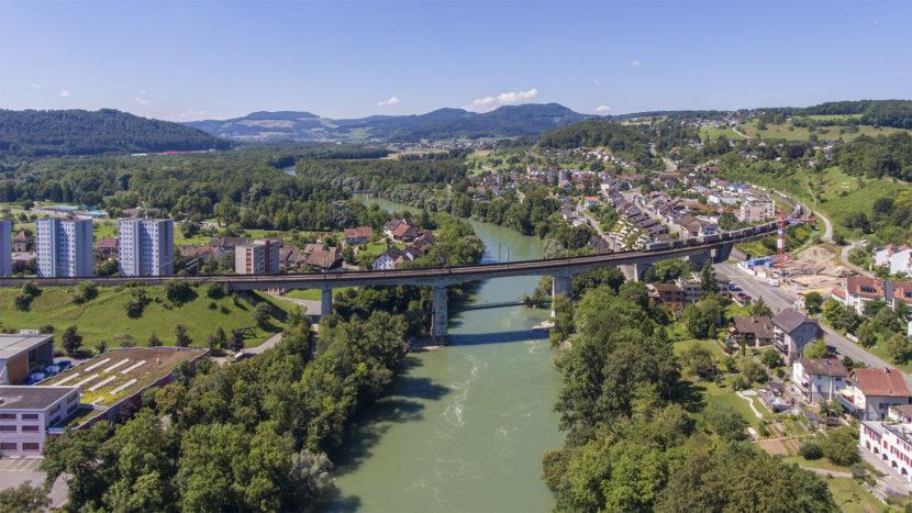 Blick stromaufwärts auf die Eisenbahnbrücke der Bözberglinie. Im Hintergrund ist das bewaldete Aaretal zwischen Schinznach und Brugg zu sehen