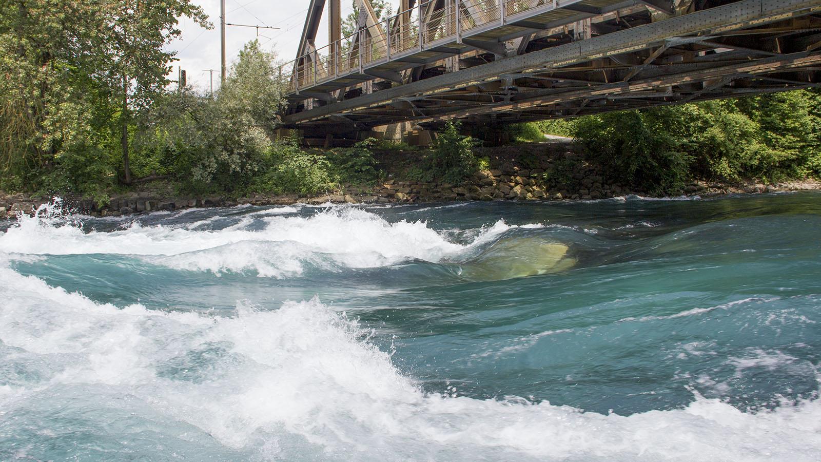 Knapp überströmter Steinquader, wenig rechts der Flussmitte